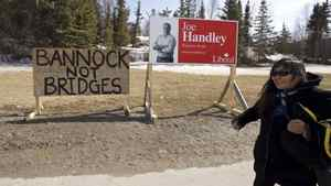 A woman walks by an election sign for Liberal candidate Joe Handley in Yellowknife on Monday. An anonymous protester's sign stands beside it. The message refers to the need for food rather than the Deh Cho Bridge that will run over the Mackenzie River.