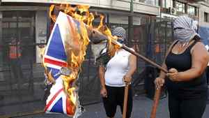 Left-wing activists burn an Union Jack flag in front of the Argentine -British Chamber of Commerce in Buenos Aires March 2, 2012. Argentine Industry Minister Debora Giorgi called on firms to stop importing UK goods in protest at Britain's position on the Falkland Islands.