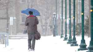 A man walks with an umbrella down a snow covered path at the University of Western Ontario in London, Ontario, January 2, 2012.