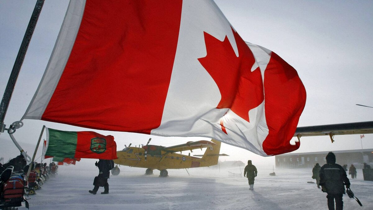 A Canadian flag flies from a snowmobile as military personnel gather during a sovereignty patrol in Eureka, Nunavut, on Mar. 31, 2007.