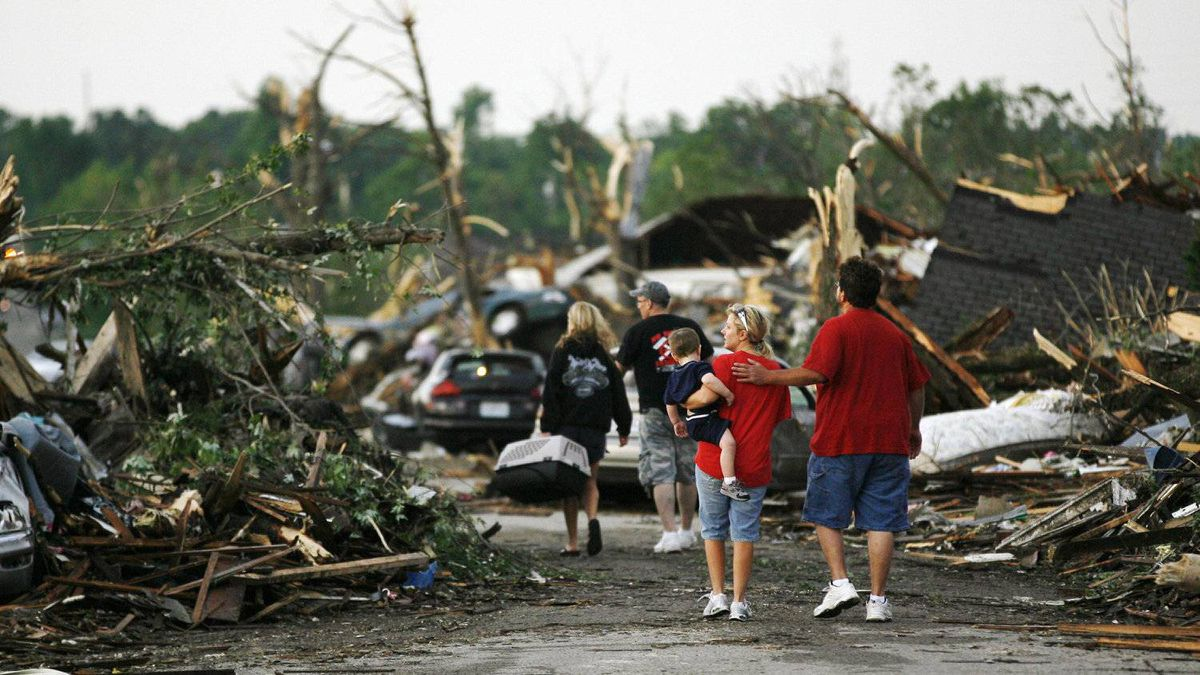 People walk through a demolished neighbourhood the day after a devastating tornado hit Joplin, Missouri May 23, 2011.