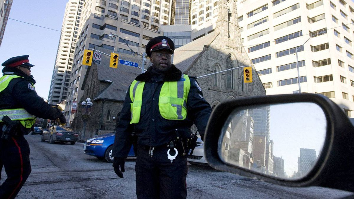 Toronto Police officers direct traffic after a power outage in Yorkville. The city's budget chief eviscerated Toronto?s approach to hiring off-duty police for special events and construction zones on Tuesday, calling the $29-million Toronto spends on the such assignments ?out of hand?