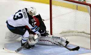 Winnipeg Jets' Kyle Wellwood (13) scores the winning goal in a shootout against Florida Panthers goalie Jose Theodore, background, in an NHL hockey game in Sunrise, Fla., Monday, Oct. 31, 2011. The Jets won 4-3.