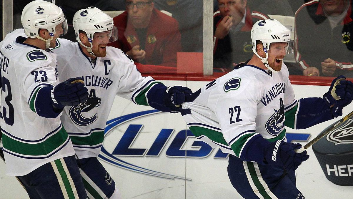 Daniel Sedin #22 of the Vancouver Canucks is grabbed by the jersey by his brother Henrik Sedin #33 after scoring a goal in the 2nd period against the Chicago Blackhawks while teammate Alexander Edler #23 joins the celebration. The Canucks won 3-2. (Photo by Jonathan Daniel/Getty Images)