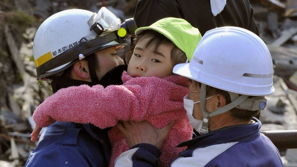 A little child is held by rescue workers after being rescued from a building at Kesennuma, northeastern Japan, on Saturday March 12, 2011.