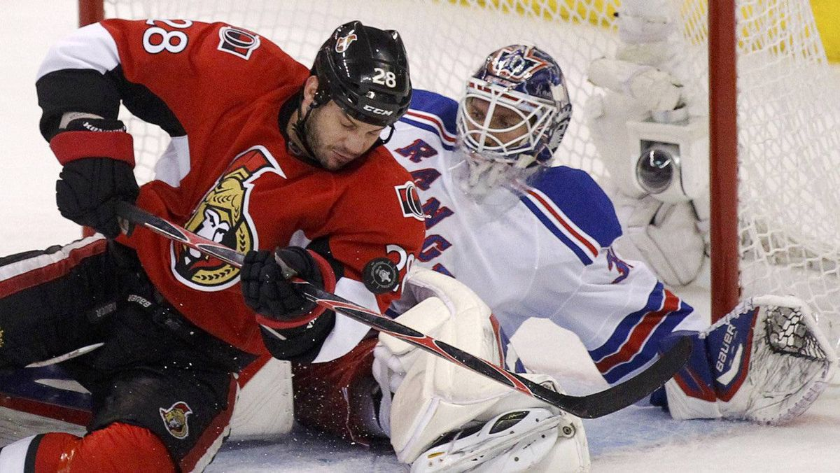 The Ottawa Senators' Zenon Konopka drives to the net on New York Rangers goalie Henrik Lundqvist in the first period.