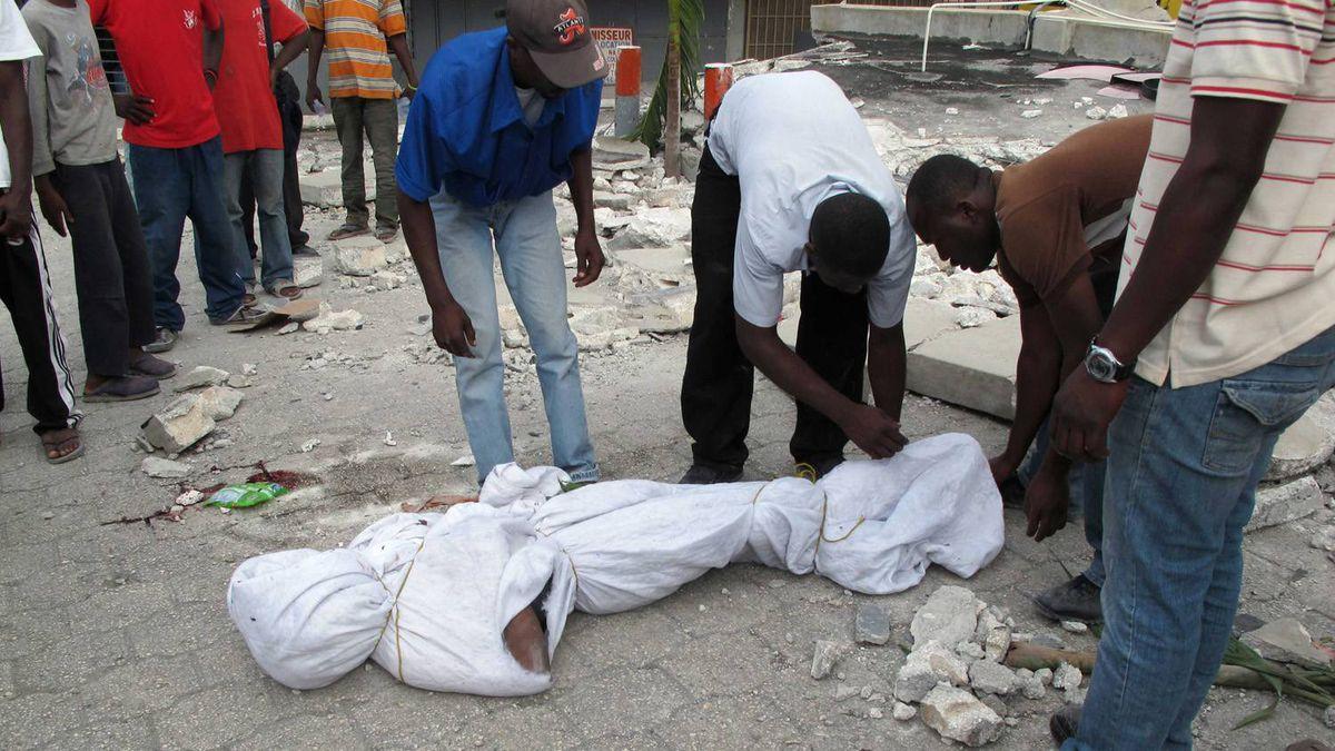 Haitians wrap of the body of an earthquake victim in Port-au-Prince. Joel Trimble/Reuters