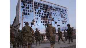 Afghan National Army soldiers stand in front a building damaged during a fierce gun battle in Helmand province, Afghanistan, on Friday.