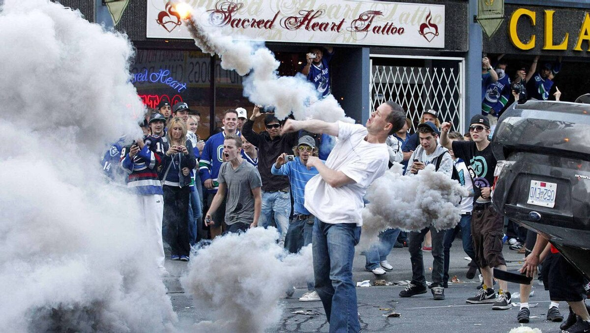 A man throws a smoking canister back at the police in Vancouver during riots after the Canucks lost Game 7 of the Stanley Cup Final to the Boston Bruins.