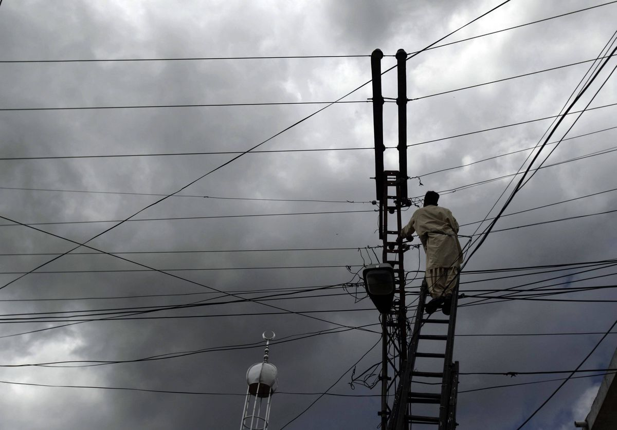 A Pakistani municipality worker fixes electrical wires in Abbottabad, Pakistan.