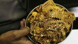 A trader holds gold jewellery at a shop in Mumbai November 3, 2009.