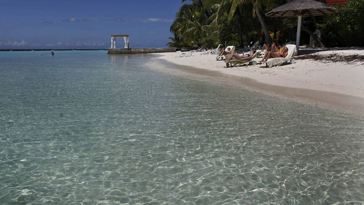 Foreign tourists sunbathe in the beach at a resort in the Kurumba island in Maldives.