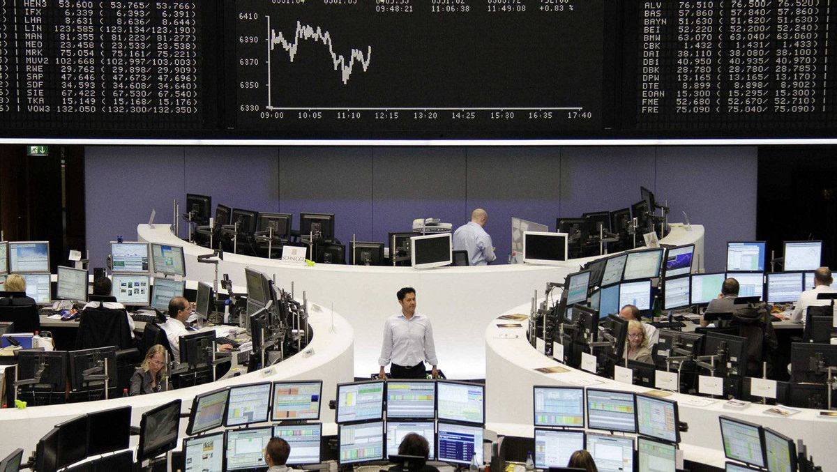 Traders work at their desks in front of the DAX board at the Frankfurt stock exchange on May 22, 2012.