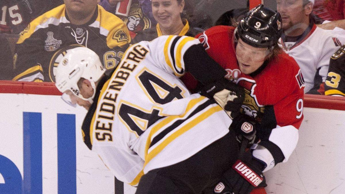 Ottawa Senators left wing Milan Michalek battles for the puck along the boards with Boston Bruins defenseman Dennis Seidenberg during second period NHL action in Ottawa, On Thursday April 5, 2012.