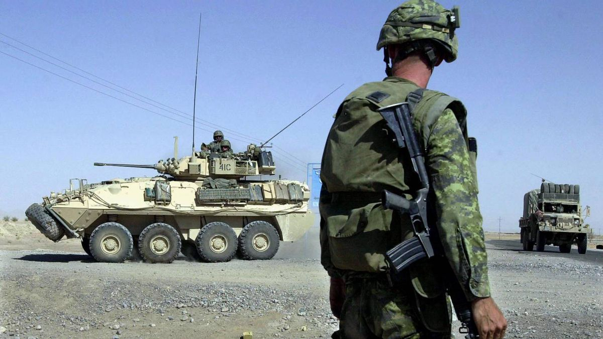 A member of the Canadian Army based at the Kandahar Air Base watches the movements of fellow soldiers riding in an armored personnel carrier as they head off of the main road leading into Kandahar, Afghanistan, and onto a desert road Sunday, June 30, 2002.
