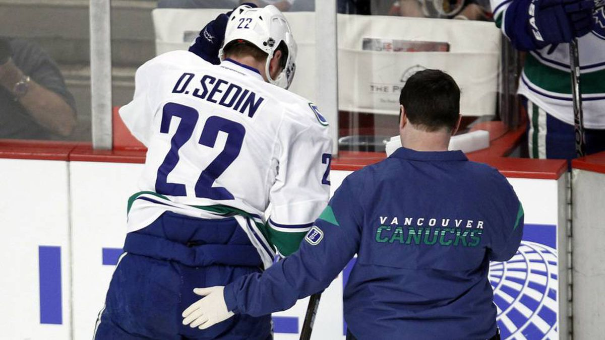 Vancouver Canucks left wing Daniel Sedin his helped off the ice in the first period of his NHL hockey game against the Chicago Blackhawks.