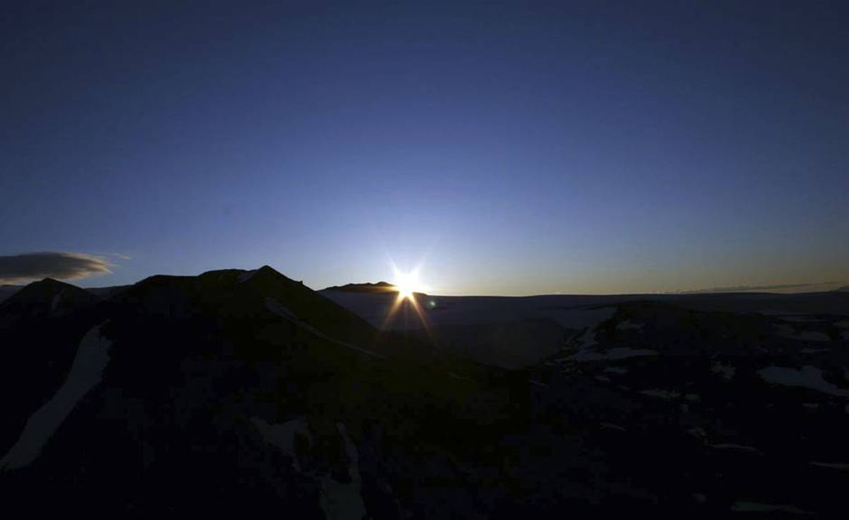 The sun sparkles over a volcanic peak. Glacier-covered peaks at Mount Edziza are visible 40 kilometres away.