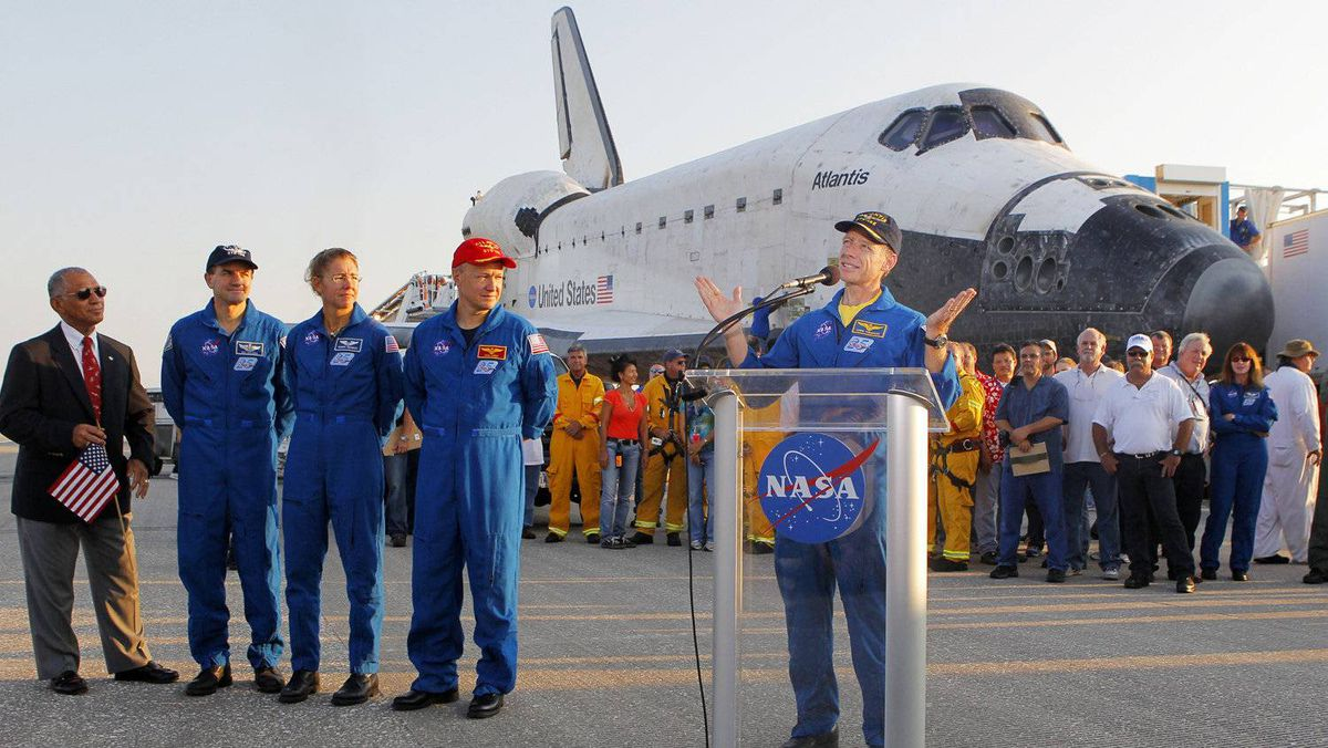 Space shuttle Atlantis commander Chris Ferguson (R) speaks on the runway July 21, 2011 at Kennedy Space Center in Florida after Atlantis landed. Listening, from L-R: NASA Administrator Charles Bolden, Atlantis mission specialists Rex Walheim, Sandy Magnus and pilot Doug Hurley
