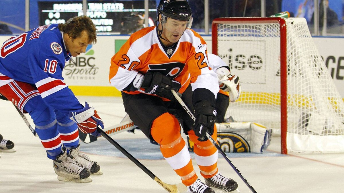 Dave Poulin, right, of the Philadelphia Flyers alumni team, clears the puck as Ron Duguay, of the New York Rangers alumni team. (AP Photo/Tom Mihalek)