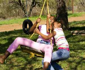 Two sisters playing on a swing.