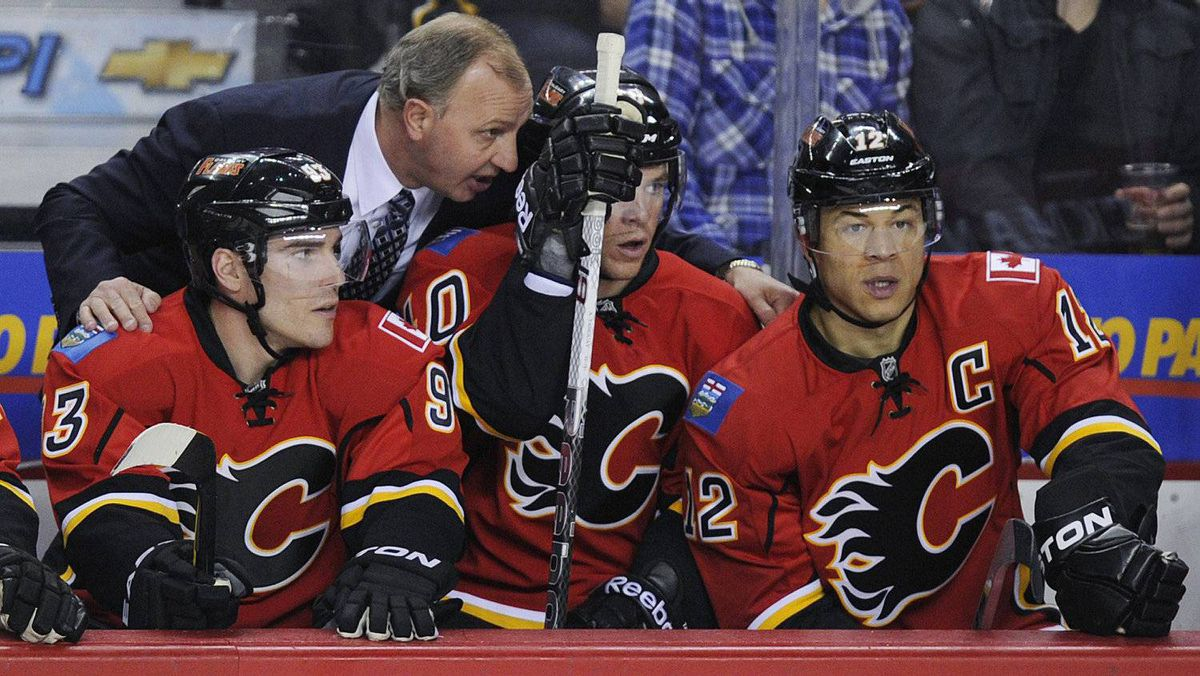 The Calgary Flames' Mike Cammalleri , left, Alex Tanguay and Jarome Iginla listen to head coach Brent Sutter's instructions during a game against the Dallas Stars in Calgary, March 26, 2012.