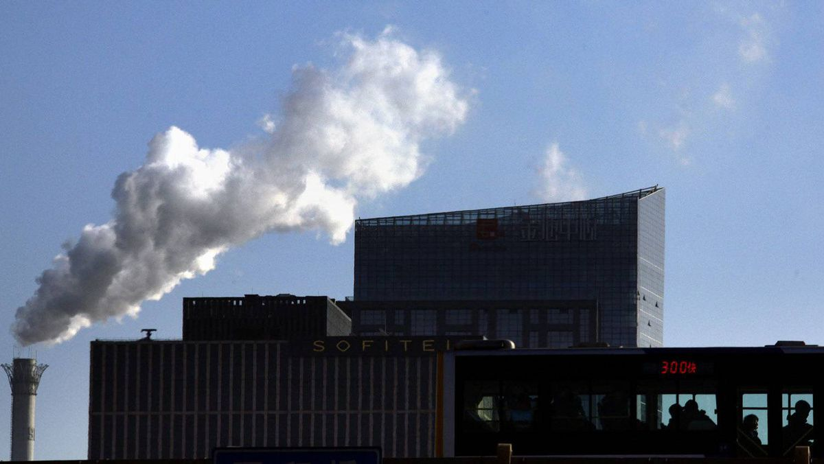 Passengers on a bus can be seen in front of a chimney for a coal-burning heating system as it billows smoke in central Beijing December 12, 2011.