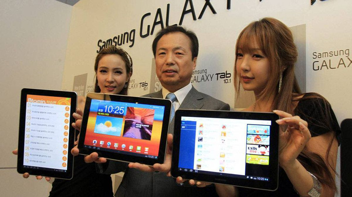 Shin Jong-kyun, president of Samsung Electronics' mobile communications business, center, and models show off the new tablet Galaxy Tab 10.1 during its unveiling in Seoul, South Korea, Wednesday, July 20, 2011 as the company launches the tablet computer on the South Korean market.