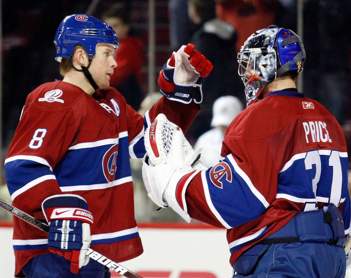 Mike Komisarek of the Montreal Canadiens congratulates teammate Carey Price after defeating the Chicago Blackhawks 4-1 at the Bell Centre Tuesday night n Montreal.