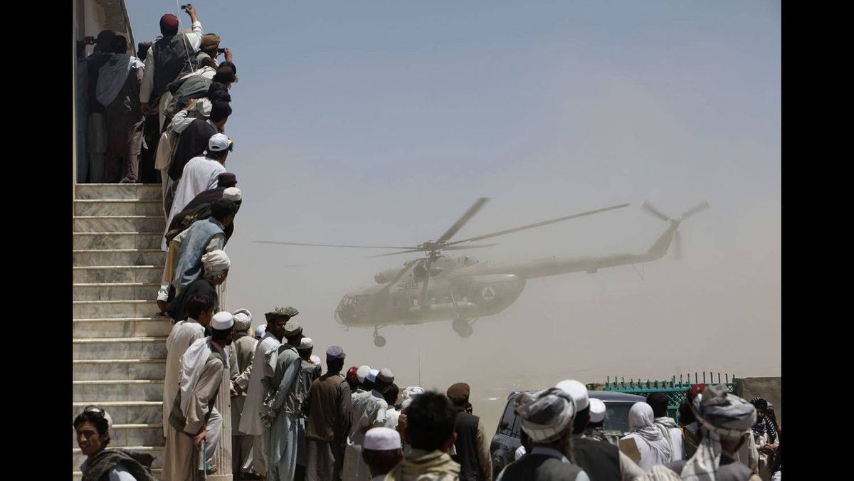 A crowd watches an Afghan National Army Air Corps helicopter carrying President Hamid Karzai during an election rally in Gardez, capital of Paktia province, south of Kabul, August 4, 2009.