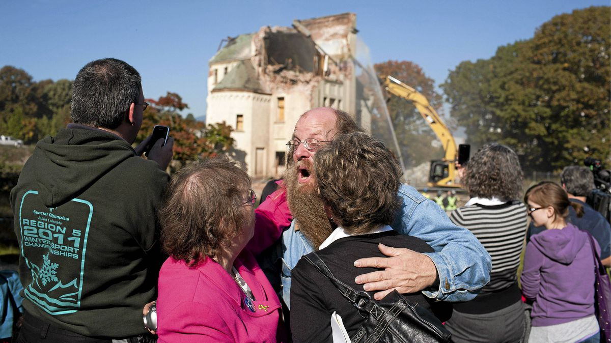 Bill MacArthur (centre), a Woodlands School survivor, along with other survivors and family members react as the reming structure of the Woodlands School is demolished in New Westminster, British Columbia, Tuesday, October 18, 2011.