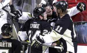 Pittsburgh Penguins' Tyler Kennedy, rear, celebrates his first-period goal with teammates Matt Cooke (24) and Jordan Staal (11) during Game 1 of an opening-round NHL hockey playoff series against the Philadelphia Flyers on Wednesday, April 11, 2012, in Pittsburgh.