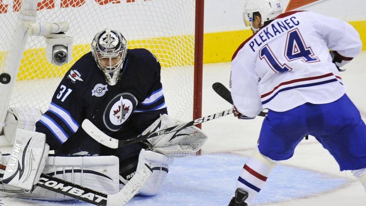 Montreal Canadiens' Tomas Plekanec (R) scores on Winnipeg Jets' goalie Ondrej Pavelec (L) during the second period of their NHL hockey game in Winnipeg, Manitoba October 9, 2011. The Winnipeg Jets are playing their first season game since the franchise left the city 15 years ago. REUTERS/Fred Greenslade
