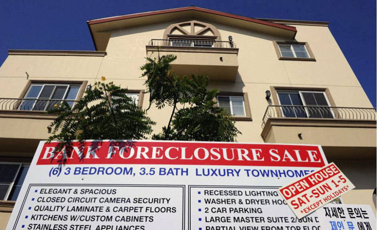 "A ""bank foreclosure sale"" sign is posted in front of townhomes in Los Angeles, Calif. U.S. banks repossessed homes at a near-record pace to drive up July foreclosures."