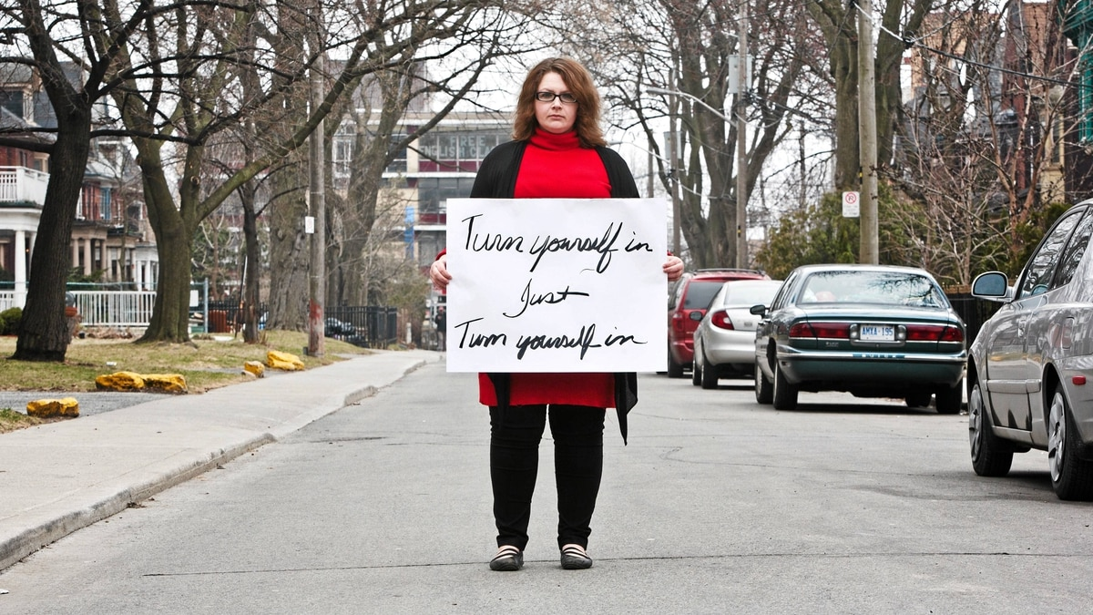 Paisley Rae holds a sign that appears in a PSA she developed in partnership with the Toronto police around the Parkdale attacks.