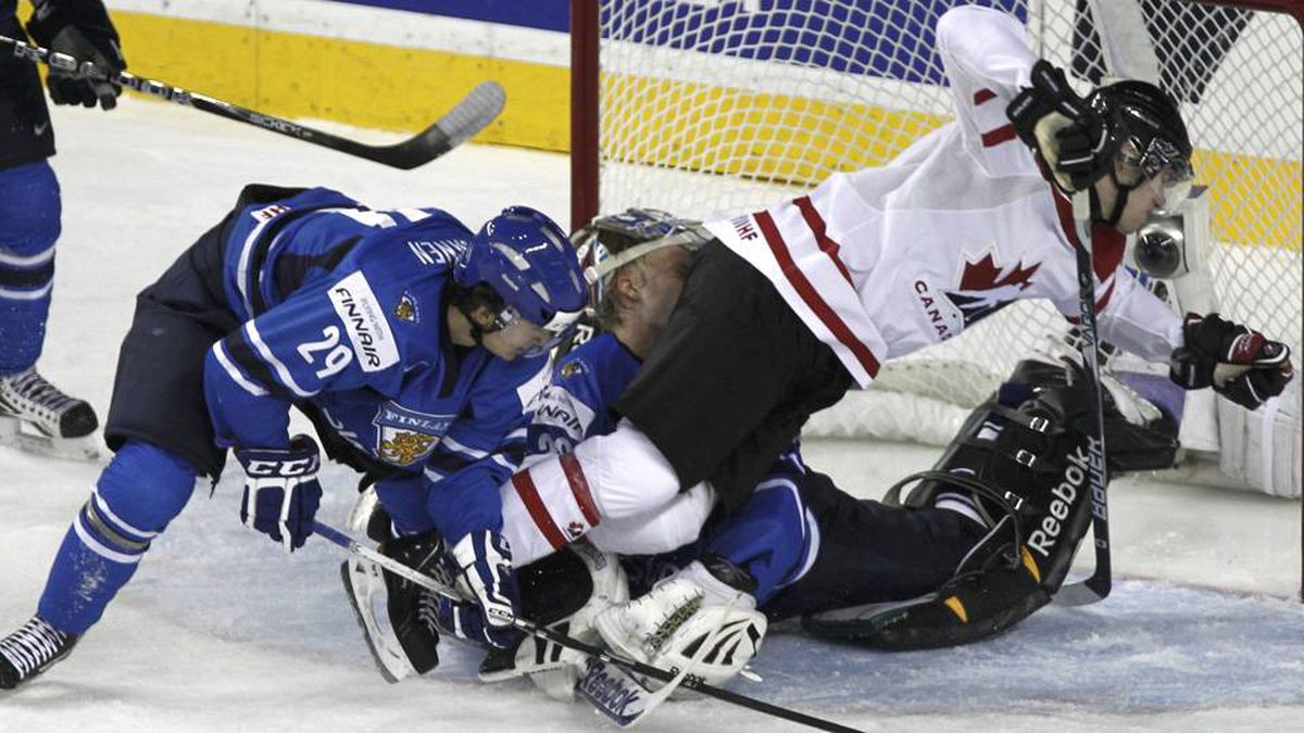 Canada's Quinton Howden collides with Finland's goalie Sami Aittokallio after being checked by Finland's Otto Paajanen (29) in the second period of play.