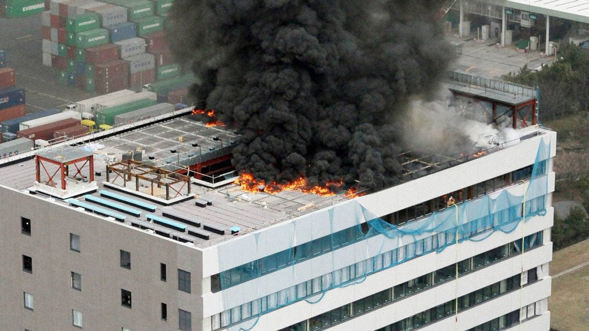 Black smoke rises from a burning building in Tokyo after Japan was struck by a magnitude 8.9 earthquake off its northeastern coast.