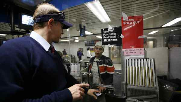 Toronto Transit Commission employee J.P. Attard attends to a line of customers at the Queen Street Subway Station in Toronto, Ontario, Canada with buying tokens, tickets and passes.