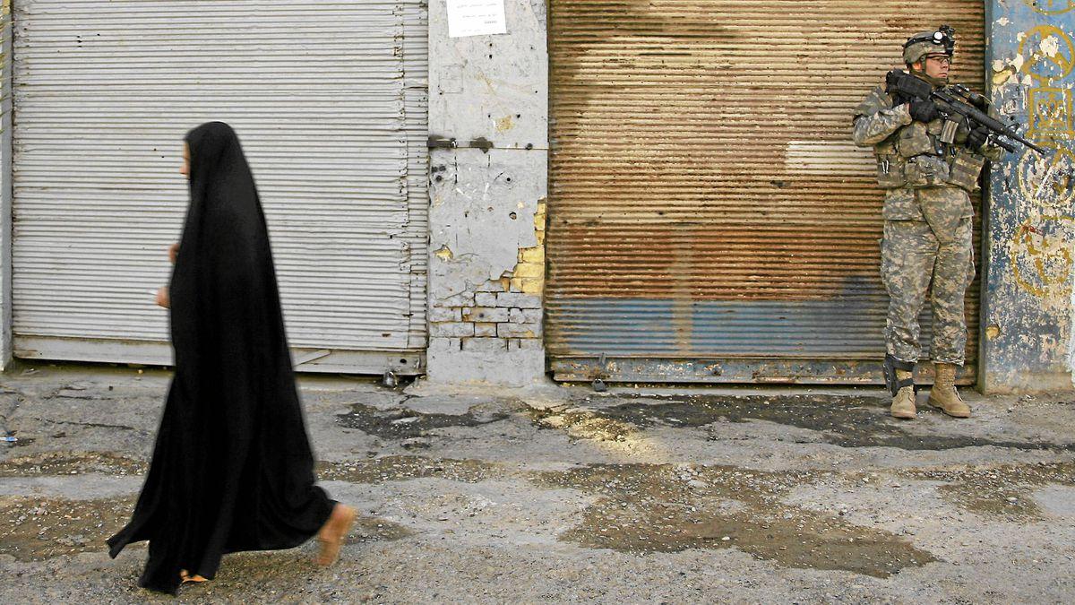 An Iraqi woman walks past a U.S. soldier on patrol in the Sheikh Ali Muslim Sunni neighbourhood in Baghdad in March, 2007.