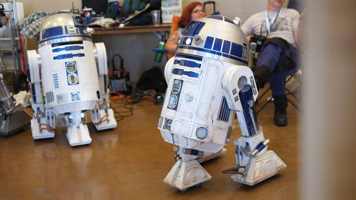 A fleet of replica R2-D2 units roam the floor.