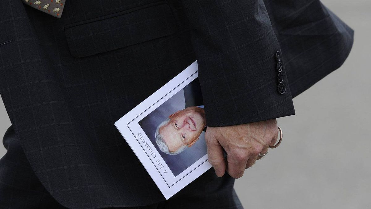 A memorial brochure is carried out of the funeral.
