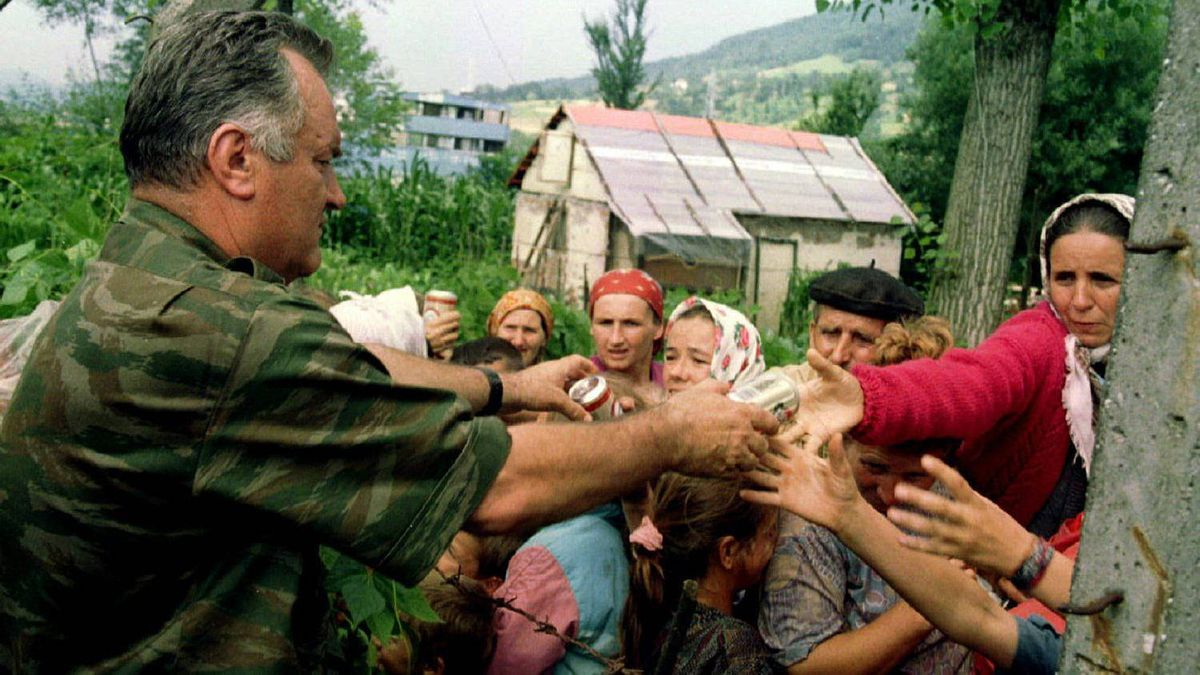 General Ratko Mladic hands out cans of beverages to Bosnian Muslims, refugees from Srebrenica, in the village of Potocari on July 13, 1995.