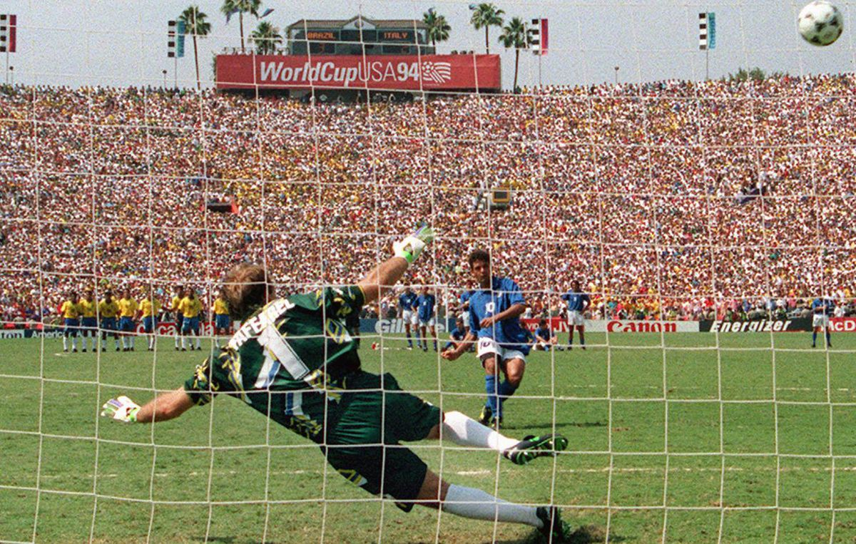 Brazilian goalkeeper Claudio Taffarel dives the wrong way as Italian midfielder Roberto Baggio's penalty kick goes over the crossbar during the shoot-out of the World Cup soccer final 17 July 1994 at the Rose Bowl in Pasadena. Baggio's miss gave Brazil a 3-2 victory (0-0 at the end of extra time) and its fourth World Cup title (1958, 1962, 1970, 1994). Getty Images/CHRIS WILKINS