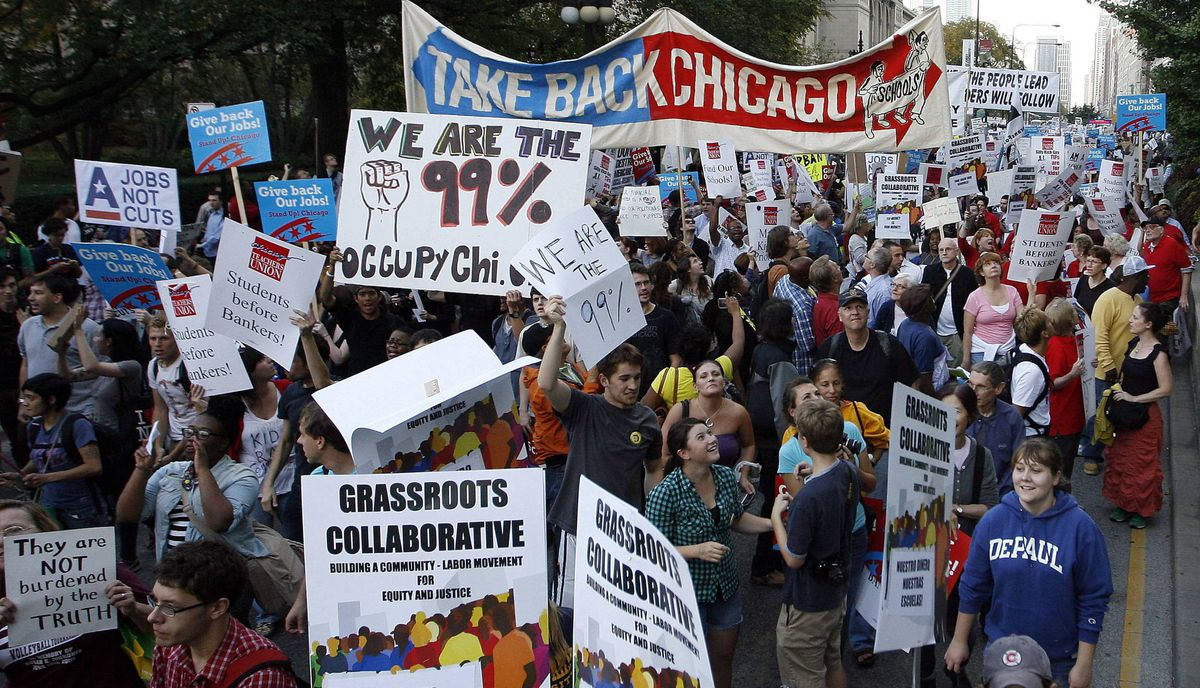 "Members of a coalition called ""Stand up Chicago"" march during a protest down Michigan Ave in Chicago October 10, 2011. Mounting anger over joblessness and income inequality snarled rush-hour traffic in downtown Chicago as hundreds of protesters marched on Monday."