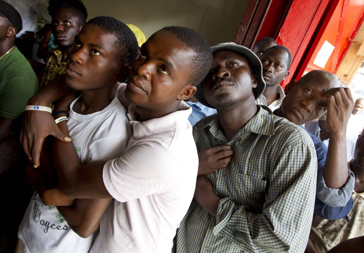 A group of men watch gather around a televison in downtown Monrovia, Liberia to watch the verdict being announced by the special international tribunal on Sierra Leone in the case against former Liberian President Charles Taylor.