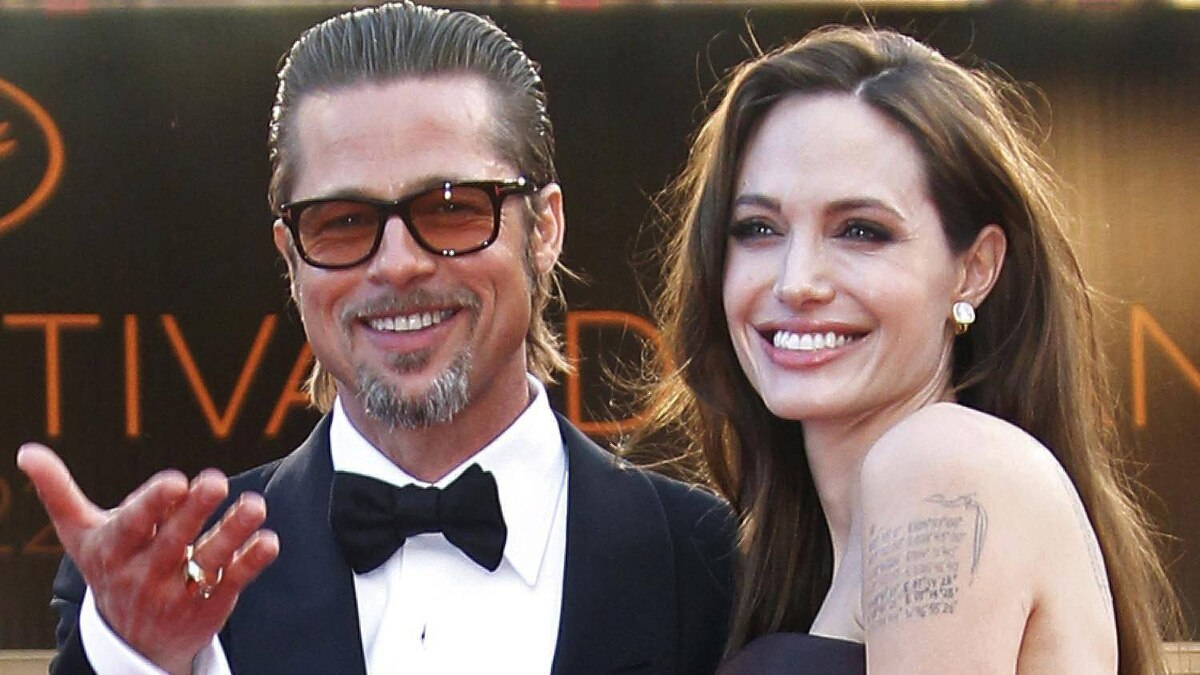 """Tattoos are pictured on the left arm of actress Angelina Jolie as she arrives with cast member Brad Pitt on the red carpet for the screening of the film """"The Tree of Life"""", by director Terrence Malick, in competition at the 64th Cannes Film Festival, May 16, 2011."""