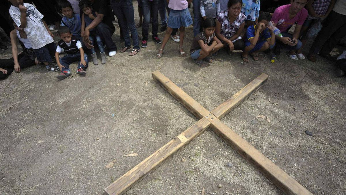 People sit around a cross during a re-enactment of the crucifixion of Jesus Christ on Good Friday in Tegucigalpa April 6, 2012.