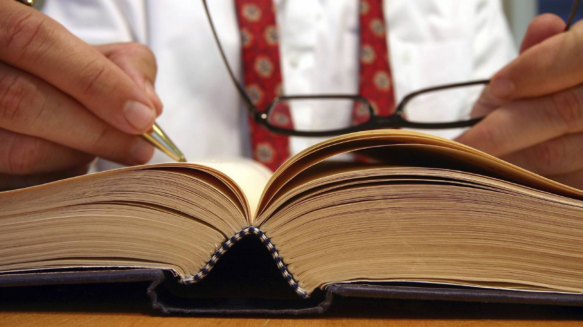 A hand holding a pen hovers over an open book, in front of a person in a white shirt and wearing an undone necktie.
