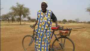 Amadou Diko, 70 years old, is bicycling with his pickaxe and shovel to the small gold pits of the Sahel region in Burkina Faso. He scavenges for gold every day because his crops have failed after a severe drought. The drought has forced a growing number of people to become dependent on the gold pits, where they sometimes dig for several days without finding even a trace of gold.