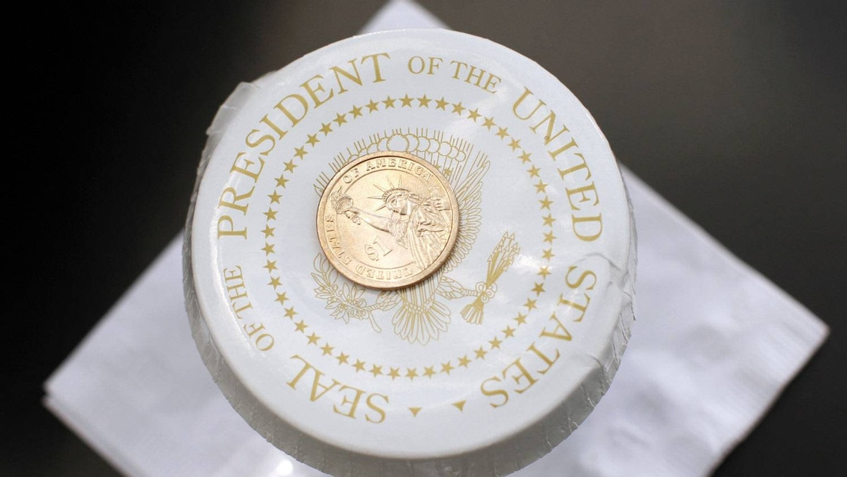 A U.S. dollar coin holds the lid top of the water glass of U.S. President Barack Obama at the Port of Tampa in Florida April 13, 2012. Mr. Obama's falling income means he will pay a 20.5-per-cent income tax rate under his own 'Buffett rule' aimed at millionaires.