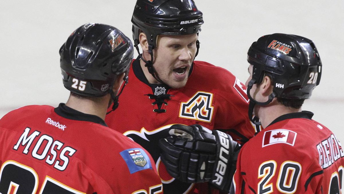 David Moss #25, Olli Jokinen #13 and Curtis Glencross #20 of the Calgary Flames celebrate a goal against the Phoenix Coyotes in third period NHL preseason action on September 29, 2011 at the Scotiabank Saddledome in Calgary, Alberta, Canada. (Photo by Mike Ridewood/Getty Images)